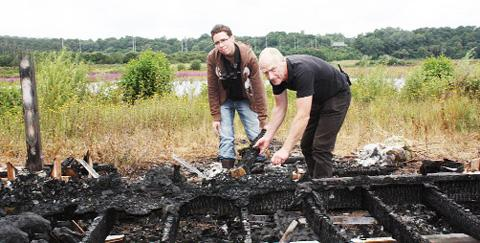 Wildlife officer Steve Ambler and Jonathan Fry examine the charred remains