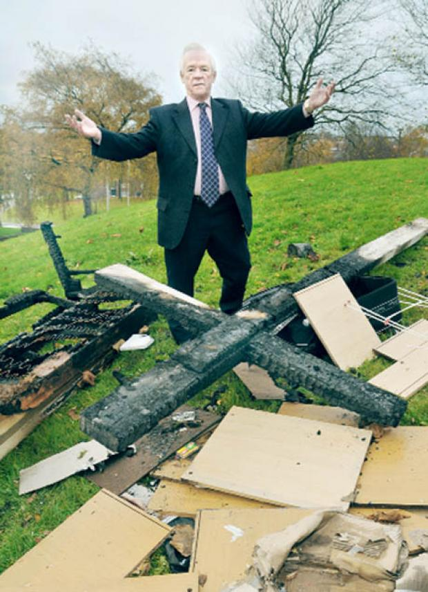 Blackburn Citizen: DISMAY Church warden George Harrison examines the remains of the cross