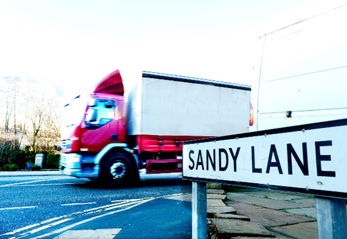 A lorry not using Sandy Lane, passes by the sign. Pleas have been made for action on Sandy Lane