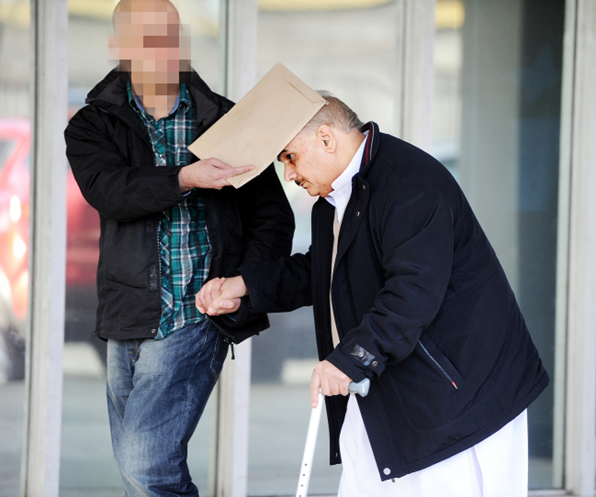 A man tries to cover the face of Rahmet Ali Raja as he leaves court after admitting benefit fraud