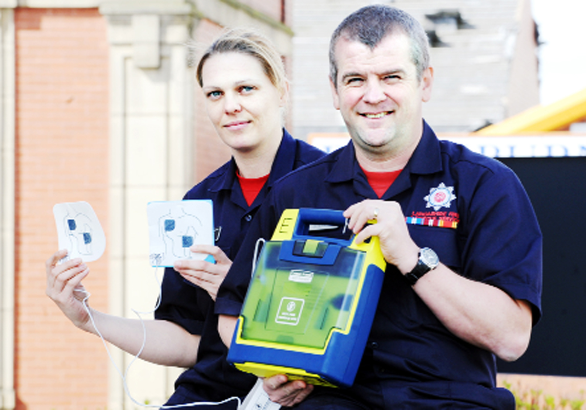 FFirefighters Tanya Birtwell and John Riley with a defibrillator