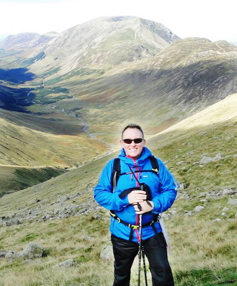 Adrian Clark looks delighted after reaching the base of Great Gable with Haystacks in the background