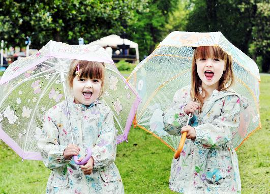 Blackburn Citizen: Twins Jasmine and Phoebe Anthony shelter themselves from last weekend's rain