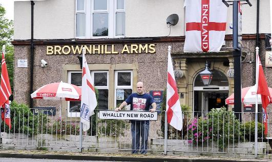 Landlord Kris Ball outside his pub with the England flags