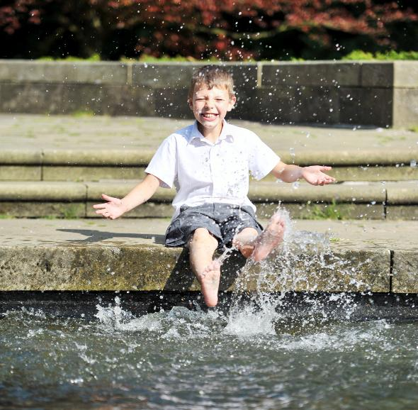 Kye Watson, eight, cools his feet in the pond in front of the cenotaph in Towneley Park, Burnley
