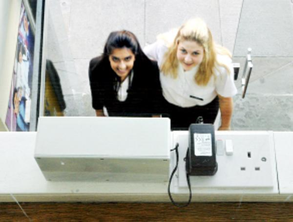 Anisha Kara and Amy Ratcliffe check out the customer counter at Whittakers Schoolwear shop
