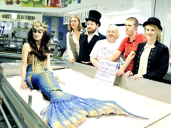 The Living Mermaid with centre, Harriet Roberts from Blackburn Heritage Festival,  Jon Turner of Mayers Fishmongers and members of A Carnival of Curiosities